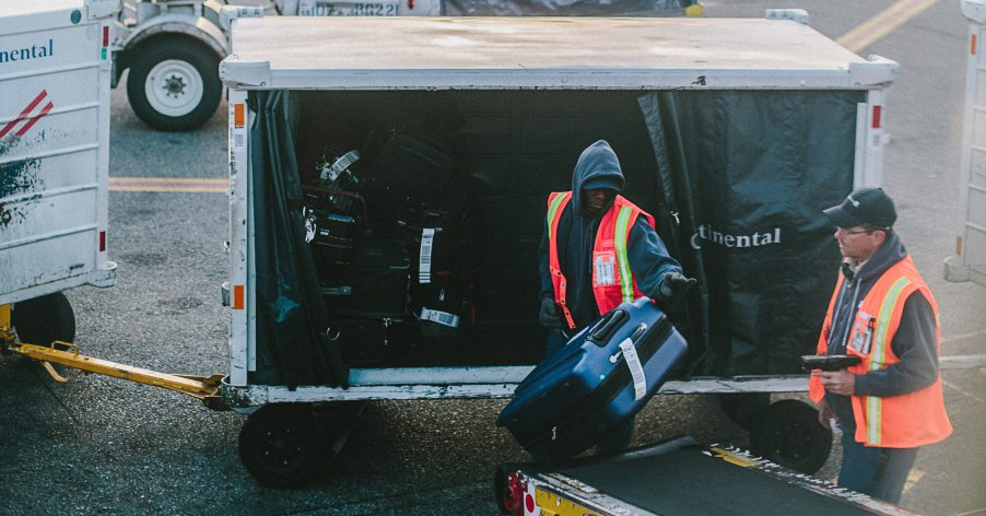two baggage handlers move bags from a cart to a conveyor belt